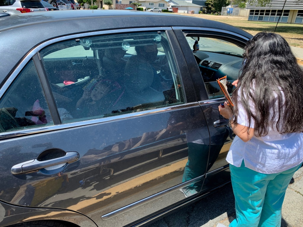 Teacher Argelia Ramos meets a new kindergarten student during a drive-by welcoming event at Park Elementary School in Hayward.