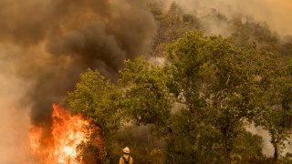 A firefighter from Santa Barbara County Fire watches a backburn just lit on Buck Mountain to fight the Carmel Fire near Carmel Valley, Calif., Wednesday, Aug. 19, 2020.