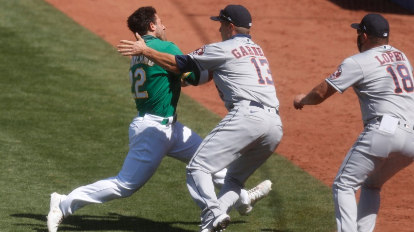 Oakland Athletics' Ramon Laureano (22) tries to run past Houston Astros' Dustin Garneau (13) while charging towards Houston hitting coach Alex Cintron, not shown, in the seventh inning at the Coliseum in Oakland.