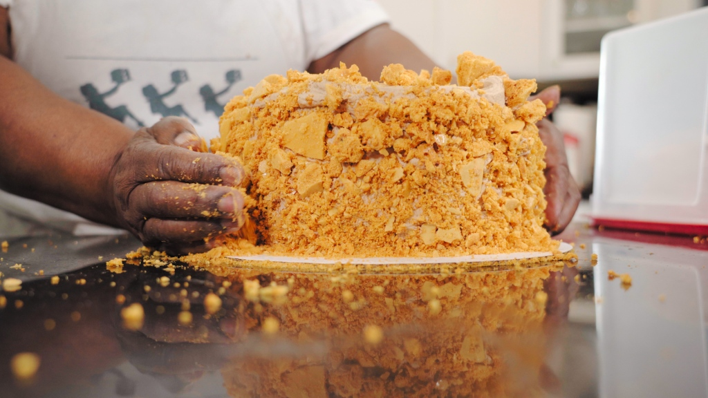 A Black woman's hands apply golden crumbly candy topping to a round cake.