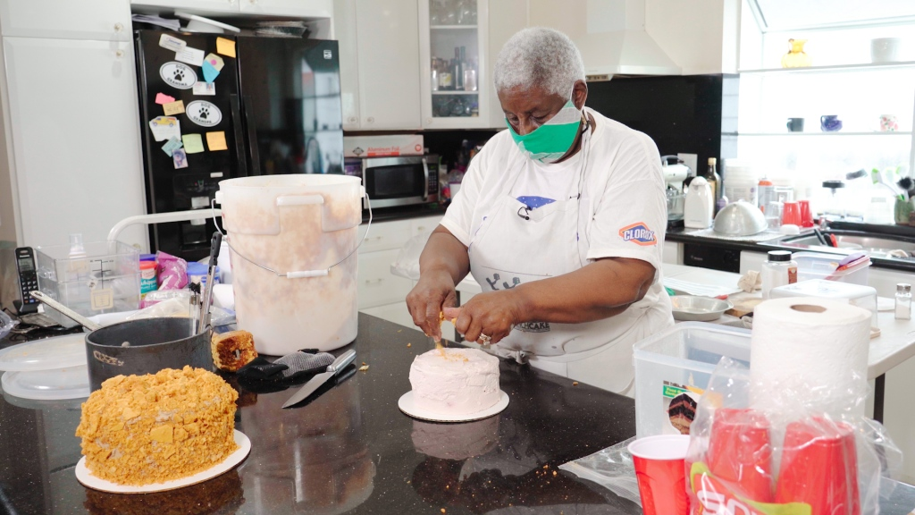 A Black woman with white hair stands in a kitchen, decorating a cake while wearing a white apron and a green mask over the lower half of her face