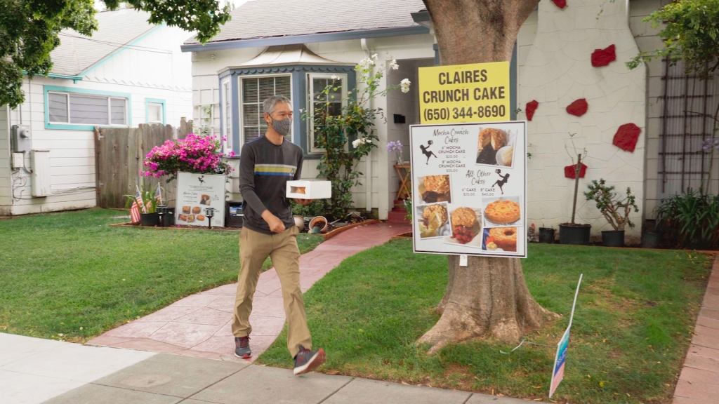 "A man leaves a house holding a bakery box with a cake in it. A sign in front of the house reads ""Claires Crunch Cake"""