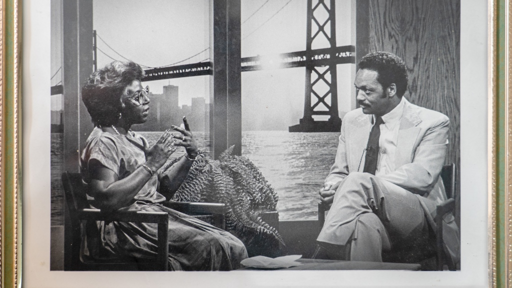 An African-American woman with short hair and glasses intervews the Rev. Jesse Jackson in a television studio against a backdrop that depicts the Bay Bridge