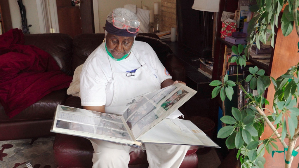 A woman in a white kitchen apron with glasses on her head sits in a chair and peruses a photo album