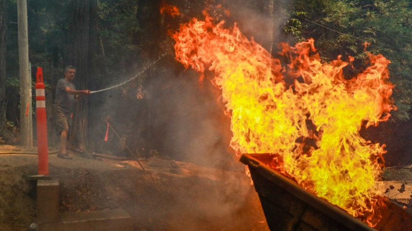 A man tries to hose down a spot fire.