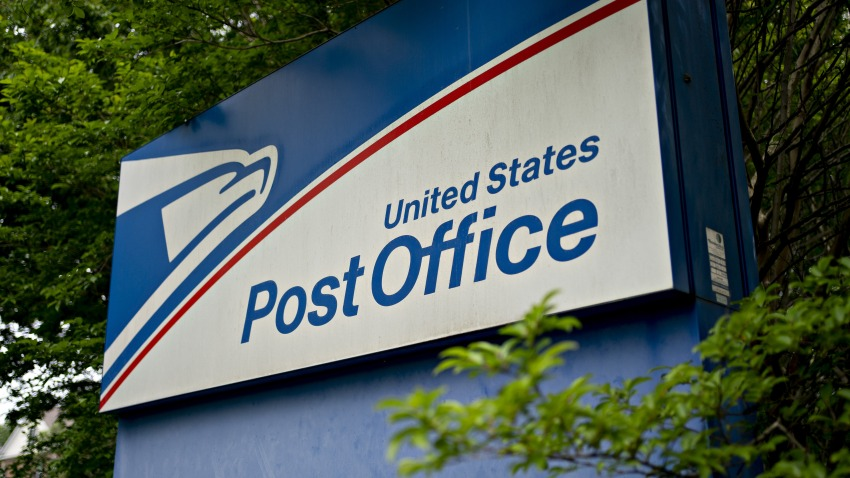 Signage stands outside a United States Postal Service (USPS) facility in Fairfax, Virginia, U.S., on Tuesday, May 19, 2020. The Postal Service in recent weeks has sought bids from consulting firms to reassess what the agency charges companies such as Amazon, UPS and FedEx to deliver products on their behalf between a post office and a customer's home, the Washington Post reported last week.