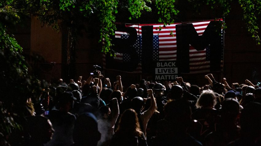 """Protesters raise their fists in solidarity as they listen to a speaker during a night of protest against racial injustice on July 31, 2020 in Portland, Oregon, as the letters BLM for 'Black Lives Matter' are seen on a flag of the United States that hangs upside down. - US federal officers will stay in the protest-wracked city of Portland until local law enforcement officials finish a """"cleanup of anarchists and agitators,"""" the US President said."""