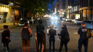 A line of protesters blocks the street in front of the Mark O. Hatfield U.S. Courthouse during a Black Lives Matter protest on August 2, 2020 in Portland, Oregon.