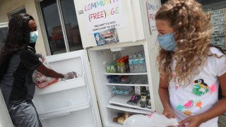 Sherina Jones (L) helps Valentina Pedon, 9, place the items her family is donating into the community refrigerator she set up in front of the Roots Collective store on August 21, 2020 in Miami, Florida. The fridge is set up to help people who need food, especially people who have lost jobs during the coronavirus (COVID-19) pandemic.
