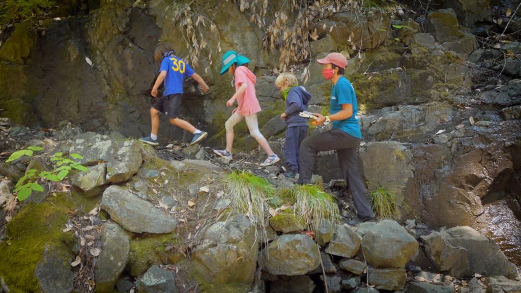 three kids and a teacher hiking over rocks