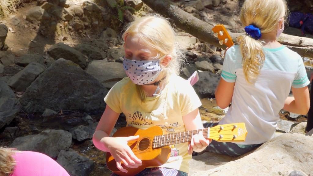 young girl strumming ukulele