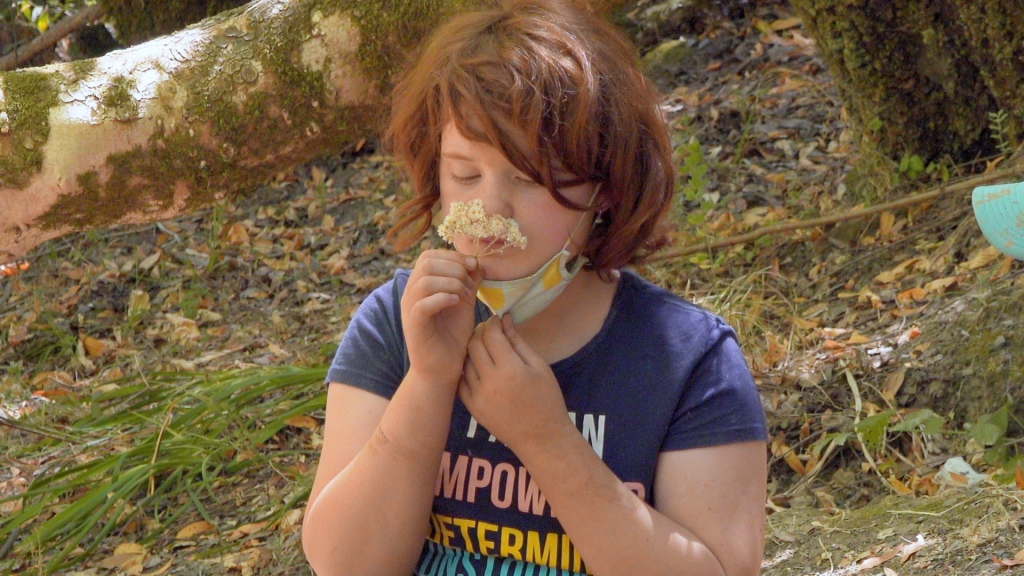a redheaded girl in a blue T-shirt smells a small handful of white wildflowers