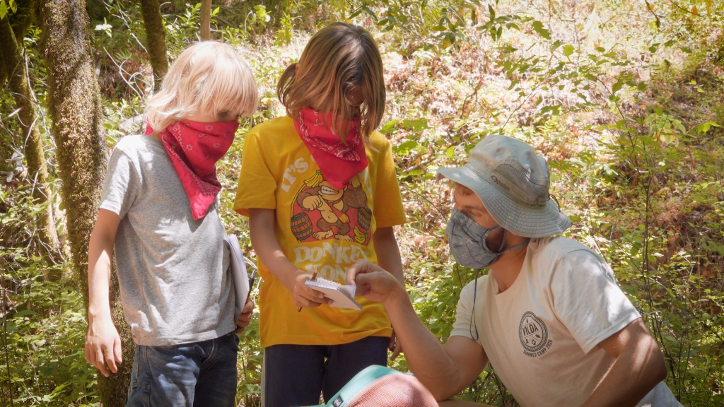 camp instructor talks to two kids wearing red bandanas on their faces.