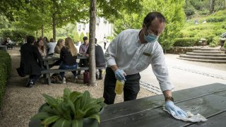 An employee wearing protective gloves and a mask cleans a table at the Buena Vista Winery tasting area in Sonoma.