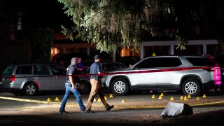 Police walk past evidence markers at a scene in Lacey, Washington