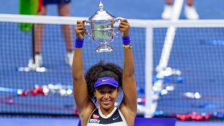 Naomi Osaka, of Japan, holds up the championship trophy after defeating Victoria Azarenka