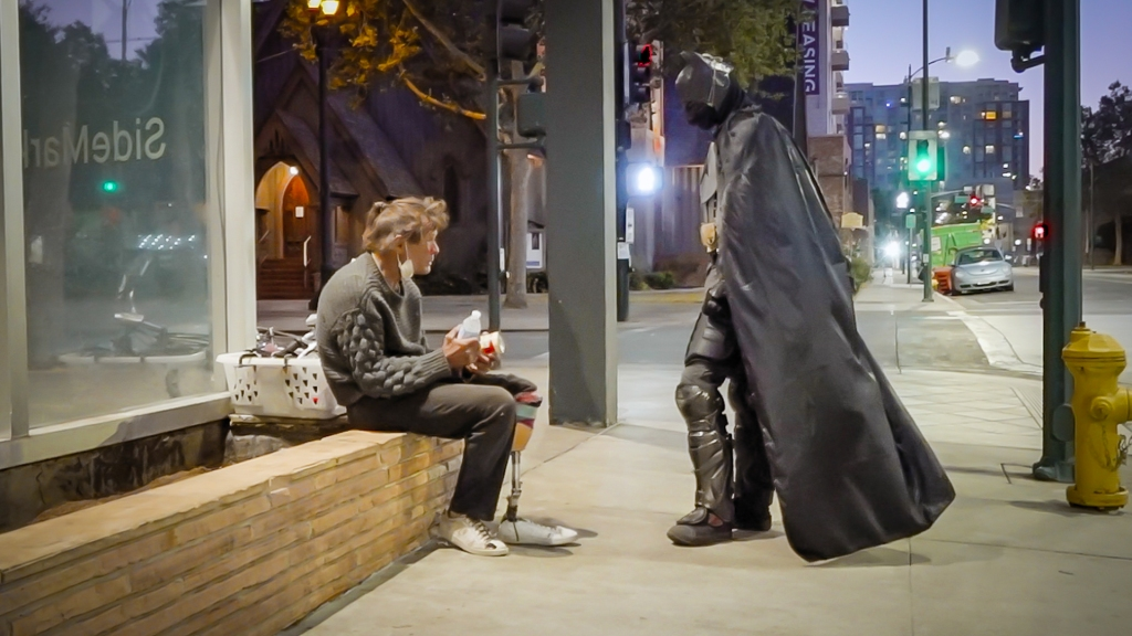 A man dressed as Batman engages in conversation with an older man seated on a low concrete wall next to a downtown building at night.