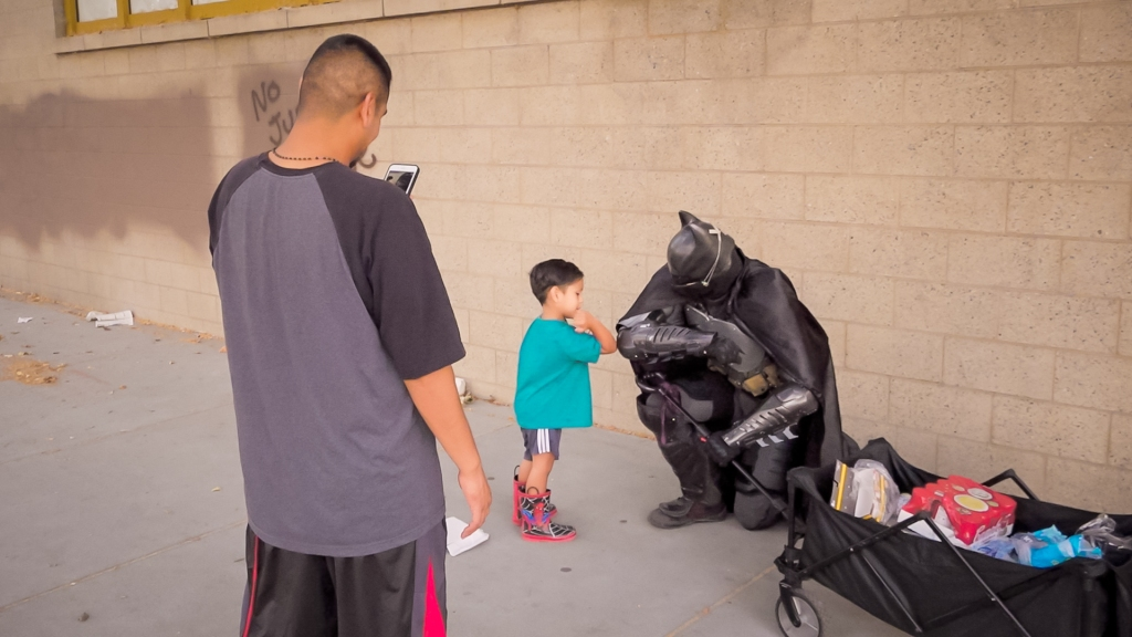 A man dressed as Batman poses for a picture with a small child. They bump elbows.