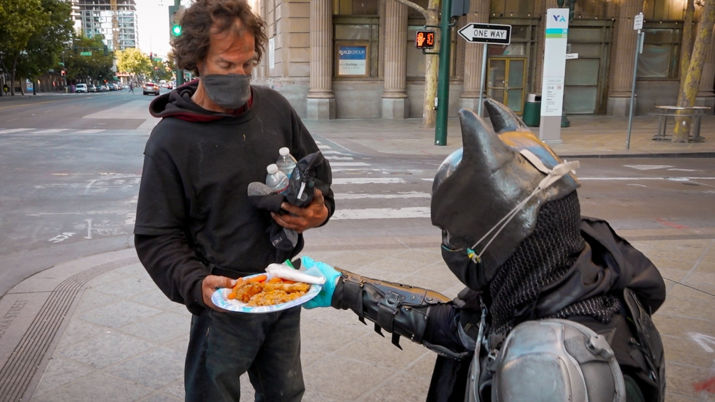 Kneeling man in a Batman helmet hands a plate of fried chicken and baked beans to a standing man in a black hooded sweatshirt