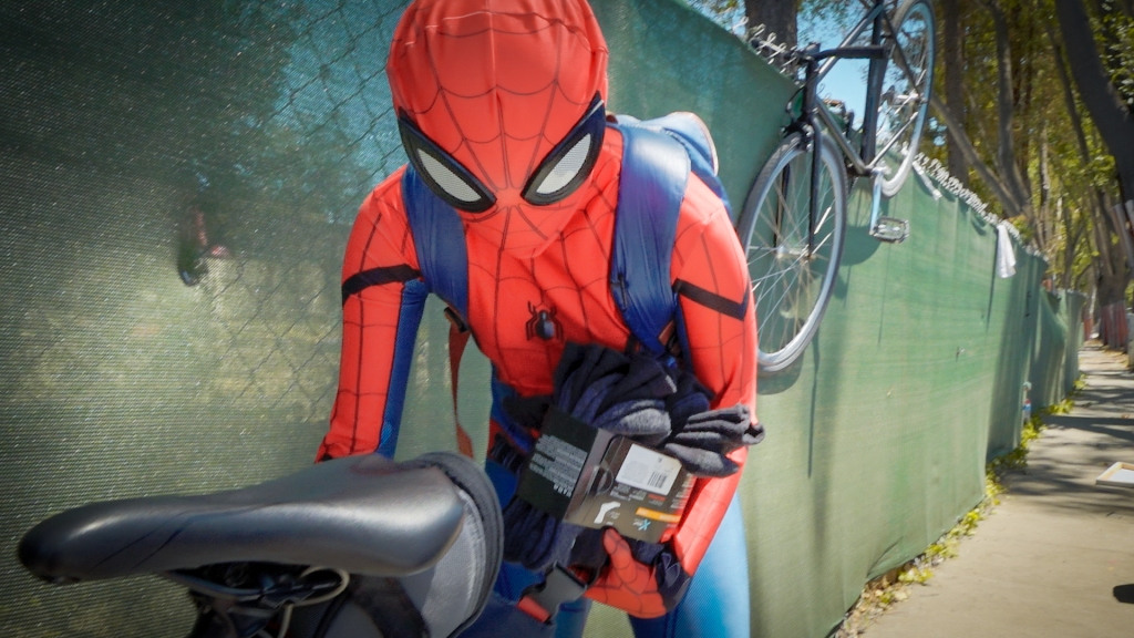 Person in a Spider-Man costume unloads socks and soda from the basket on the back of a bicycle