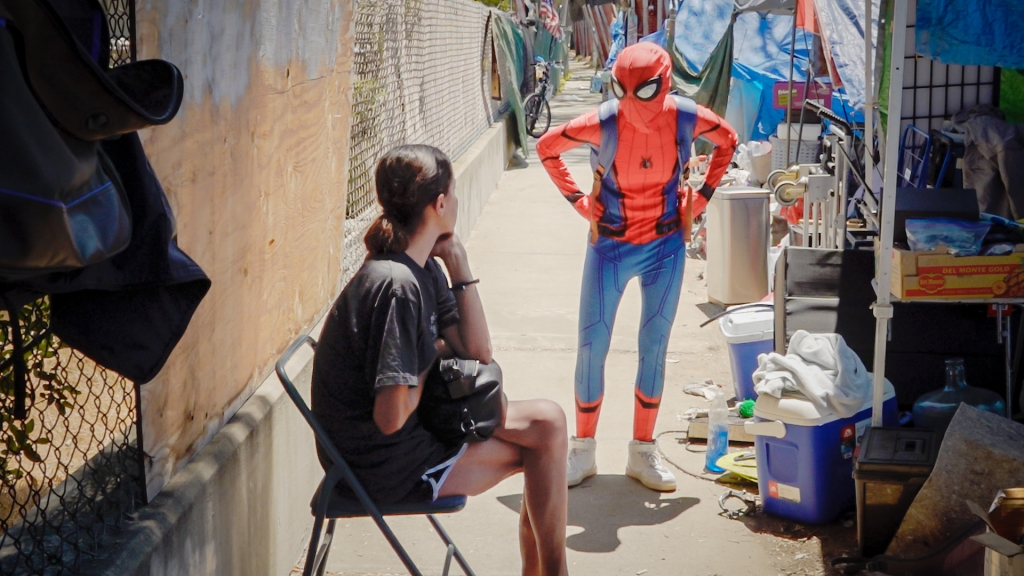 A person in a Spider-Man costume stands on the sidewalk, talking to a woman seated in a folding chair.