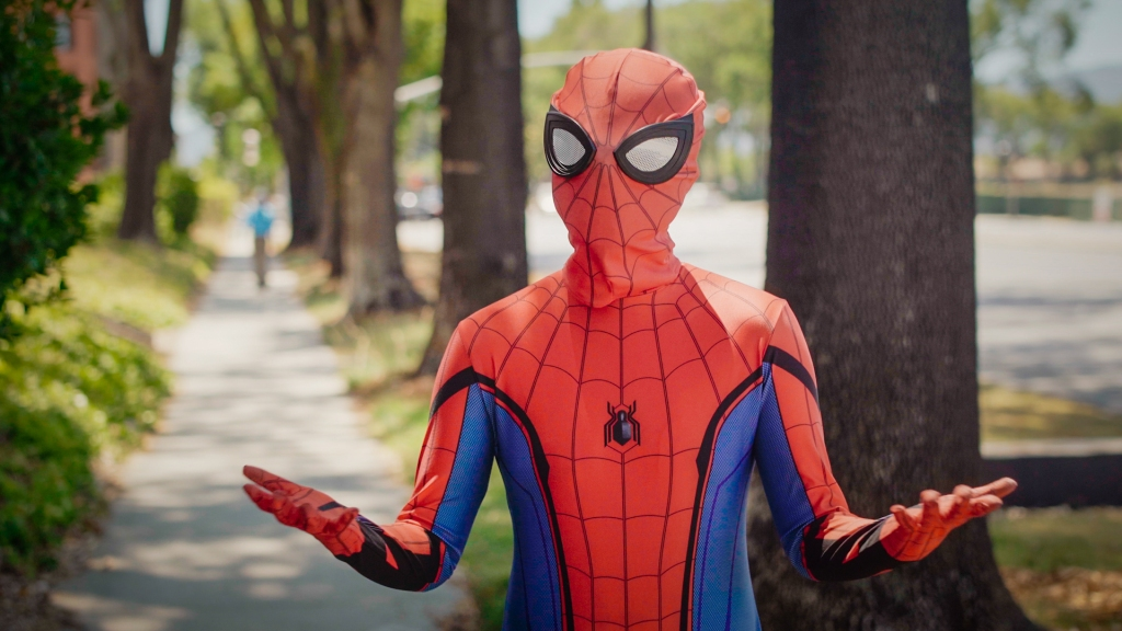 A person in a spider-Man costume talks to the camera