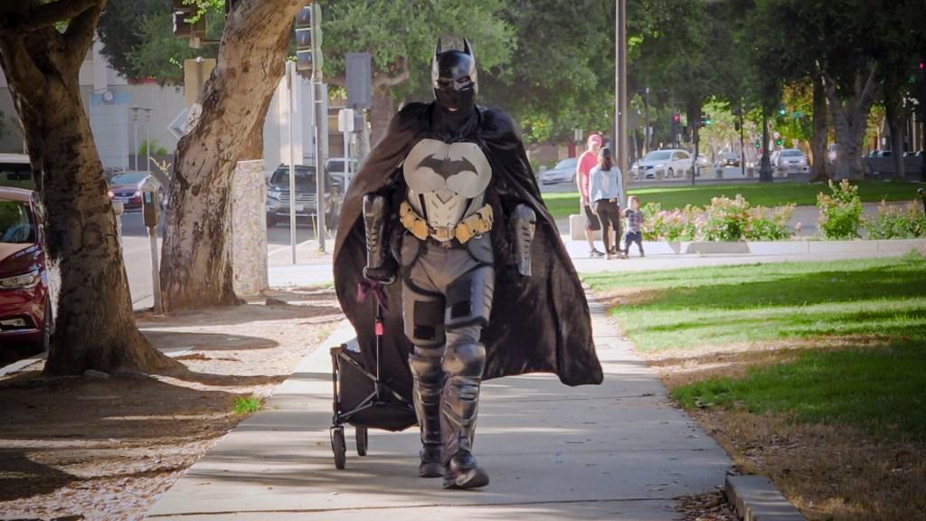 A man dressed as Batman pulls a small wagon through a park