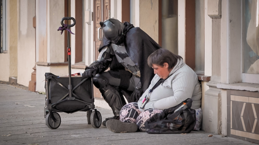 A man in a Batman costume kneels next to a woman sitting on the sidewalk against a building.