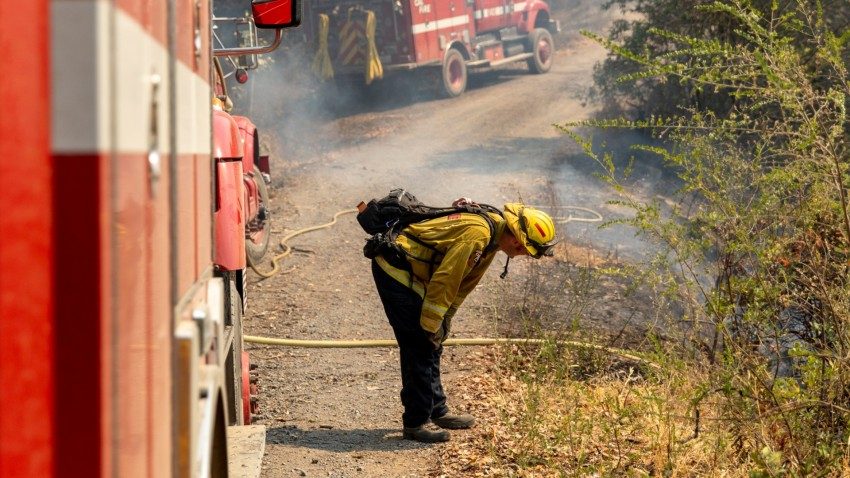 A firefighter leans over in an exhausted state.