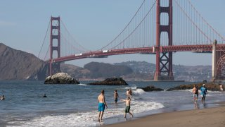 People cool off on Baker Beach in San Francisco.