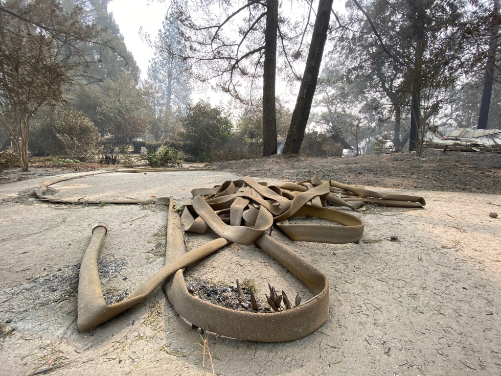 A tangle of firehoses outside the Working family's home in St. Helena shows the epic fight firefighters waged to save the home.