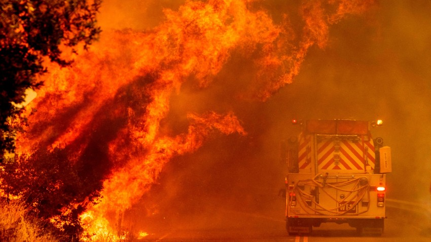 A fire truck drives through flames as the Hennessey fire continues to rage.
