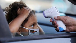 In this Sept. 2, 2020, file photo, a student receives a temperature check before leaving the car to enter STAR Eco Station Tutoring & Enrichment Center in Culver City, California.