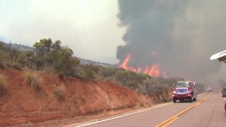Flames are seen off the side of a road in the Japatul Valley area.