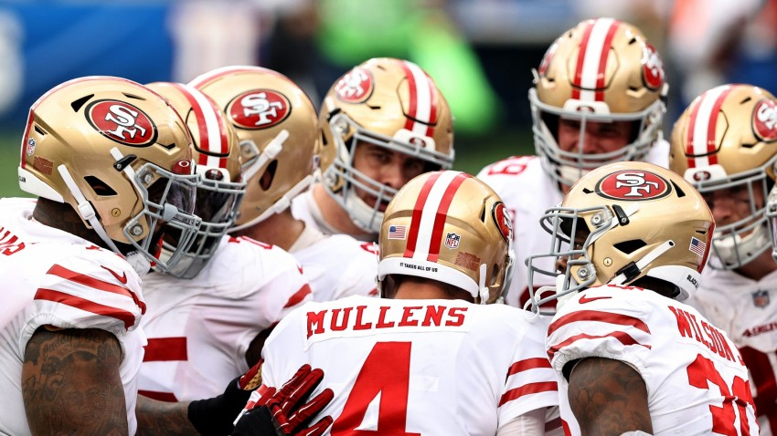 Nick Mullens of the San Francisco 49ers and the offense huddles.