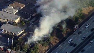 A brush fire burns along Interstate 580 in Oakland.