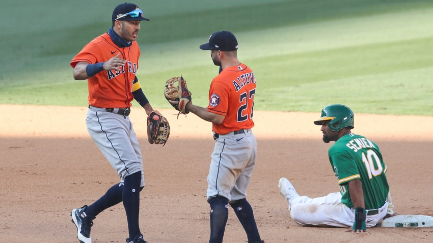 Jose Altuve of the Houston Astros high fives Carlos Correa while Marcus Semien of the Oakland Athletics sits on second base.