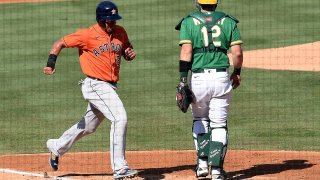 Michael Brantley of the Houston Astros scores a run against Sean Murphy of the Oakland Athletics.