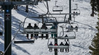Skiers and snowboarders ride a high speed chairlift.