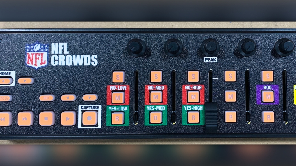 "Closeup of a button controller that says ""NFL Crowds"" on it, and has a cluster of red and green buttons labeled Yes/No, Low/Med/High"