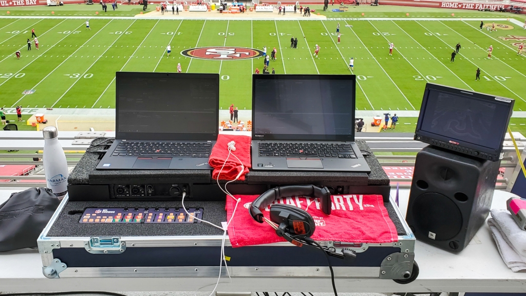Two laptops in a road case sit on a balcony overlooking the 49ers' football field at Levi's Stadium.