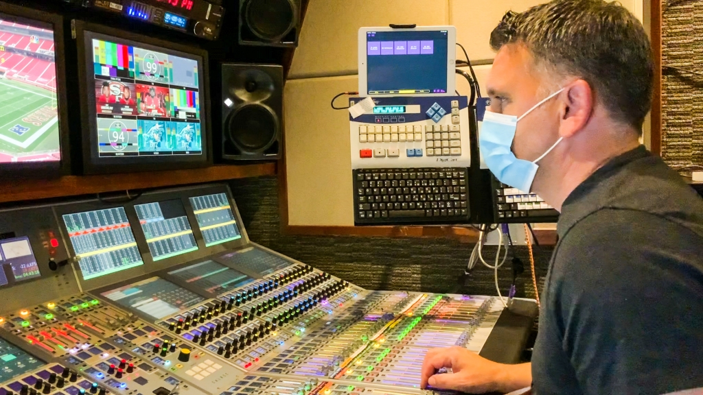 A man wearing a surgical mask sits at an audio mixing board
