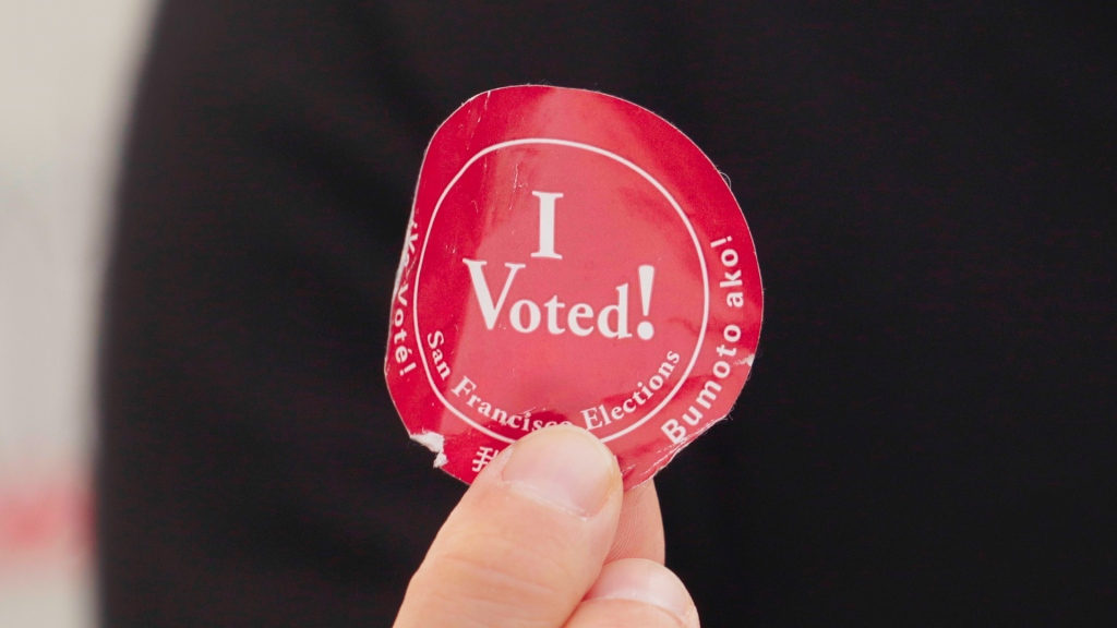 """circular red sticker that says """"I voted"""""""