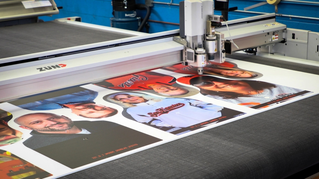 a CNC cutting machine cuts out head-and-shoulders photos from a rectangular batch of 8 printed on a large white board