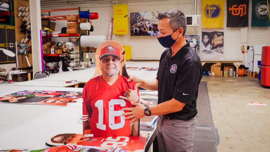 a man in warehouse points out features of a large cut-out 49ers fan photo