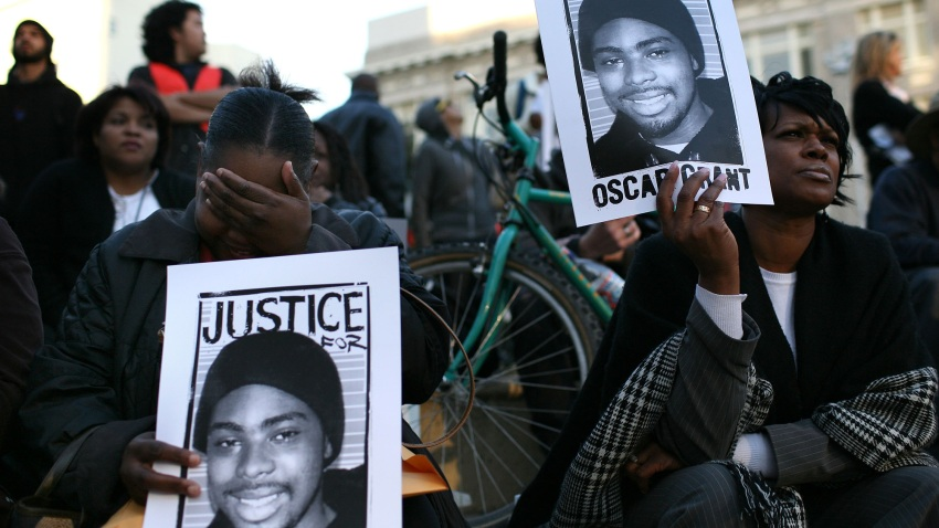 Protestors carry signs with a picture of slain 22-year-old Oscar Grant III during a demonstration at Oakland City Hall.
