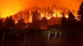 The Glass Fire burns in the hills near a vineyard.