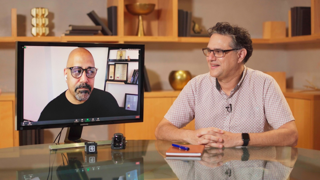 Two men looking at each other -- on the left, one is inside a computer screen. On the right, the other is sitting next to that screen at a glass table.