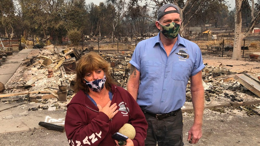 "Kevin Conant and his wife, Nikki, look at the debris of their home and business, ""Conants Wine Barrel Creations,"" after the Glass/Shady Fire completely engulfed it, Sept. 30, 2020, in Santa Rosa, Calif."