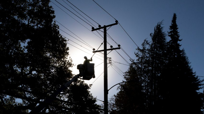 In this Oct. 15, 2020, file photo, PG&E line inspector Kevin Ogans works to clear lines so crews can begin removing a tree that crashed into live power lines along Mountain Boulevard in the Montclair Village neighborhood of Oakland, California.